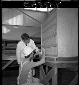 B.C. Vocational School; Carpentry Trades student inside the Carpentry shop measuring wood with an...