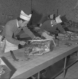 Meat cutting, 1968;  two students sawing large pieces of meat