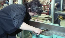 BCIT Women in Trades; carpentry, woman using bench tool (sander?) [2 of 5 photographs]