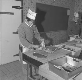 Meat cutting, 1968;  a student cutting a piece of meat