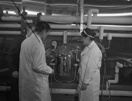 Food Processing Technology, 1966; three people looking at the pressure gauge of a  piece of food ...