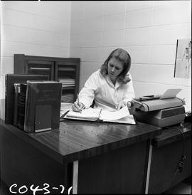 BC Vocational School Commercial Program; woman at a medical office desk and recording information...