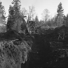 Heavy duty equipment operator, Nanaimo ; a man operating an excavator moving dirt ; piles of dirt...