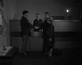 Hotel Motel, 1966; man standing behind a staged hotel welcome desk, woman standing next to two me...