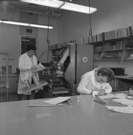 BCVS Graphic arts ; woman working at a desk ; woman using a paper collator