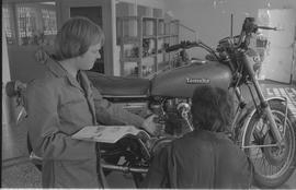 Pacific Vocational Institution ; a student and instructor looking at a Yamaha motorcycle