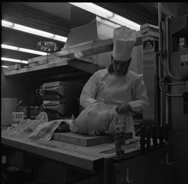 BC Vocational School Cook Training Course ; a student preparing a whole turkey to be cooked [2 of 2]