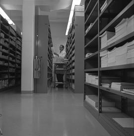 BCVS Graphic arts ; a man with a cart shelving stacks of paper ; shelves of books