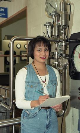 Female First Nations student standing near a milk pump pasteurizing equipment [1 of 3 photographs]