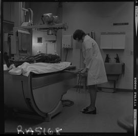 Medical radiography, 1968; woman in lab coat adding film to an x-ray generator ; manikin lying on...