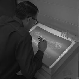 Map drafting, Victoria, 1968; man using magnifying glass to look at a drafted map on a light table