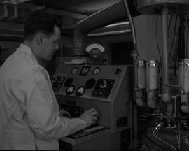 Instrumentation, 1964; man in a lab coat turning a dial on a piece of instrumentation equipment [...
