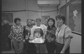 Staff posing with pumpkin carving of a crying baby [1 of 2 photographs]