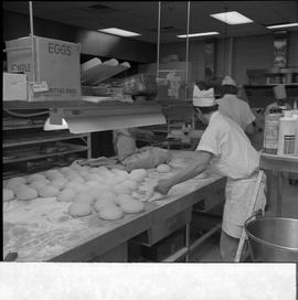 BC Vocational School Cook Training Course ; student rolling dough at a table filled with rolled d...