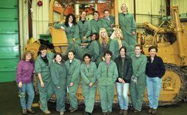 BCIT women in trades; heavy duty, students in uniforms standing in front of a bulldozer [3 of 9 p...