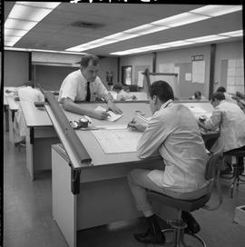 BC Vocational School drafting course ; instructor talking to a student sitting at their drawing d...