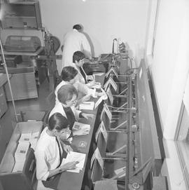 BCVS Graphic arts ; people adding folding papers to the conveyor for a staple binding machine ; m...