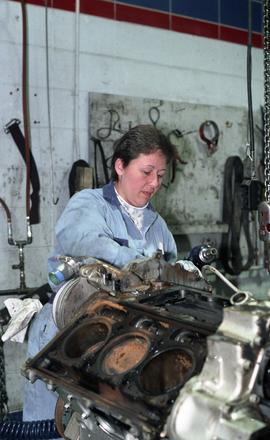 BCIT women in trades; BC Transit, student in uniform while working on a motor engine [6 of 8 phot...