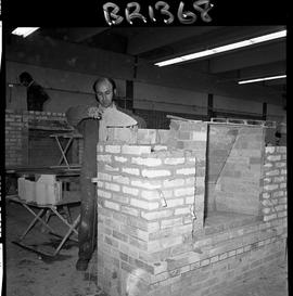 B.C. Vocational School image of a Bricklaying student building brick fireplace in the shop