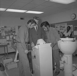 Navigation, 1968; three men looking at a piece of navigation equipment [2 of 2]