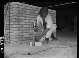B.C. Vocational School image of a Bricklaying student cutting a brick
