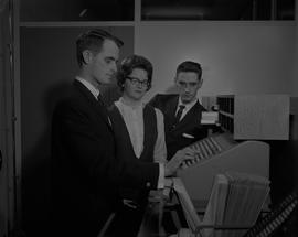 Hotel Motel, 1966; a man and a woman watching a man using a cash register at a staged hotel recep...