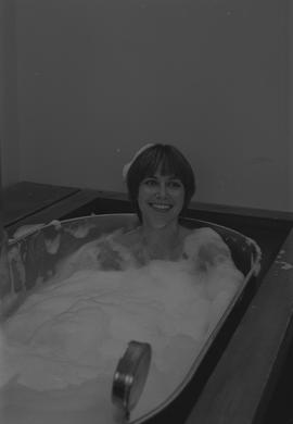 Woman covered in bubbles, sitting in a bubble filled metal tank