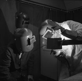 Welding, Terrace, 1968; two people wearing a face shields, one man watching the other welding two...