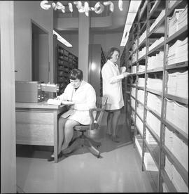 BCVS Graphic arts ; woman working at a desk ; woman organizing paper on a shelf [1 of 3]
