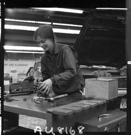 BC Vocational School image of a woman student in the Automotive Mechanics program working on vehi...