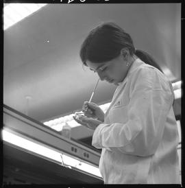 Medical laboratory technology, 1968; student in lab coat examining contents in a petri dish [2 of 2]