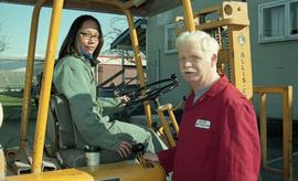 BCIT women in trades; forklift training, instructor beside a student driving a forklift [3 of 8 p...