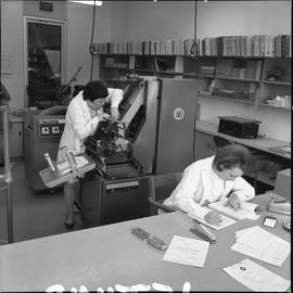 BCVS Graphic arts ; woman working at a desk ; woman fixing a paper collator