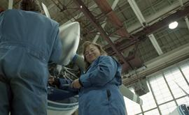 Canadian women at work; woman in uniform working on a jet engine with tools inside a hangar [4 of...