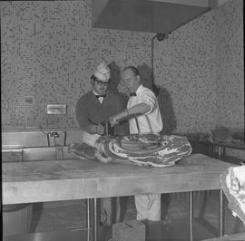 Meat cutting, 1968;  instructor helping a student use a saw to cut a large piece of meat