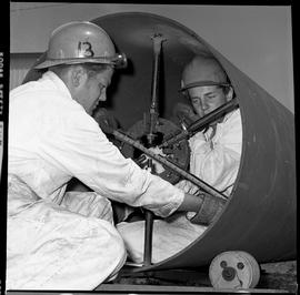 B.C. Vocational School image of two Boilermaker students measuring the inside of a large metal pipe