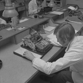 Office Machine Mechanic, 1968; man repairing a calculator ; people working in background
