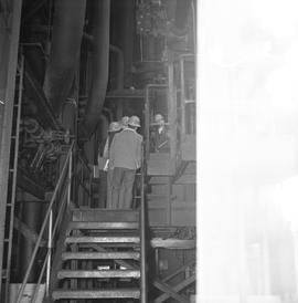 Forestry, Wood fiber BCIT tour, November 26, 1965; men wearing hard hats walking through a factory