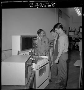 BC Vocational School image of an instructor and two students in the Appliance Servicing program; ...