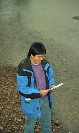 Male First Nations BCIT graduate standing outside holding a notebook [12 of 16 photographs]