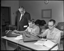 BC Vocational School Commercial Program; two students using adding machines ; instructor supervising