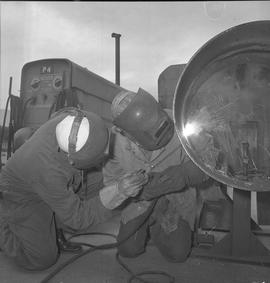 Welding, Prince George, 1968; two people kneeling next to a pipe welding using the same welder eq...