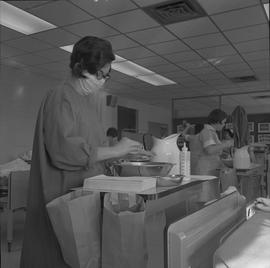 Practical nursing, Prince George, 1968; nurse wearing a face mask washing her hands ; people work...