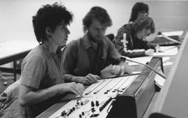 Broadcast Communication, 1980s(?); woman working at a broadcast control table, other students wor...