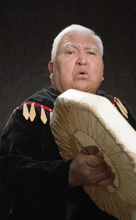 Bob George, First Nations elder, in First Nations garment playing an instrument [16 of 36 photogr...
