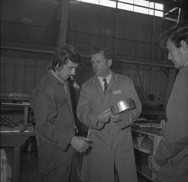 Sheet metal, 1968; instructor holding a circular piece of metal, two students standing next to hi...