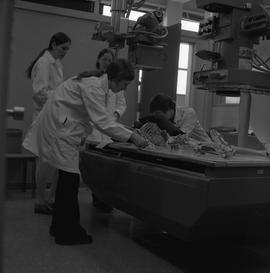 Medical radiography, 1968; two people placing a skeleton on an x-ray table ; two people observing
