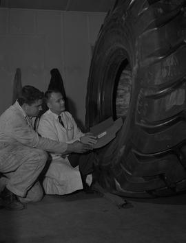 Tire repair, Nanaimo, 1967; instructor and student kneeling next to a large tire