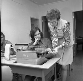 BC Vocational School Commercial Program; instructor checking a student's typewritten work [1 of 2]