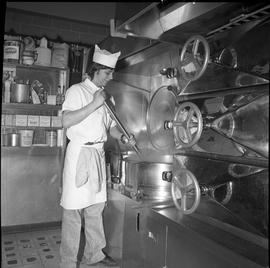 BC Vocational School Cook Training Course ; student stirring food in a large industrial pot